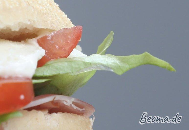 Zwischen zwei Brötchenhälften: Schinken, Salatblatt, Mozzarella und Tomate